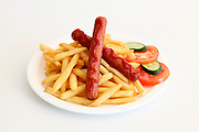 2 hot dog sausages with chips vegetables and ketchup on white