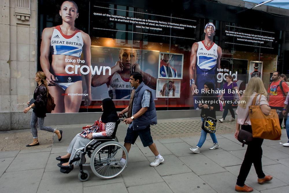 Passers-by walk beneath the inspiring images of Team GB gold medallist heptathlete Jessica Ennis and long jumper Phillips Idowu adorn the exterior of the Adidas store in central London's Oxford Street, during the London 2012 Olympic Games. The ad is for sports footwear brand Adidas and their 'Take The Stage/Crown' campaign which is viewable across Britain and to Britons who have been cheering these athletes who have been winning medals in numbers not seen for 100 years. Their heroic performances have surprised a host nation who until the victories, were largely anti-Olympics - now adoring their darling Ennis and her good looks.