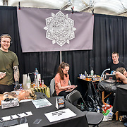 William Jones, Tattoo a client at The Great British Tattoo Show, on 26 May 2019, London, UK.