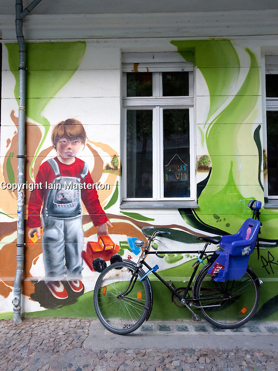 Mural of children playing painted on outside wall of kindergarten in Prenzlauer Berg in Berlin Germany