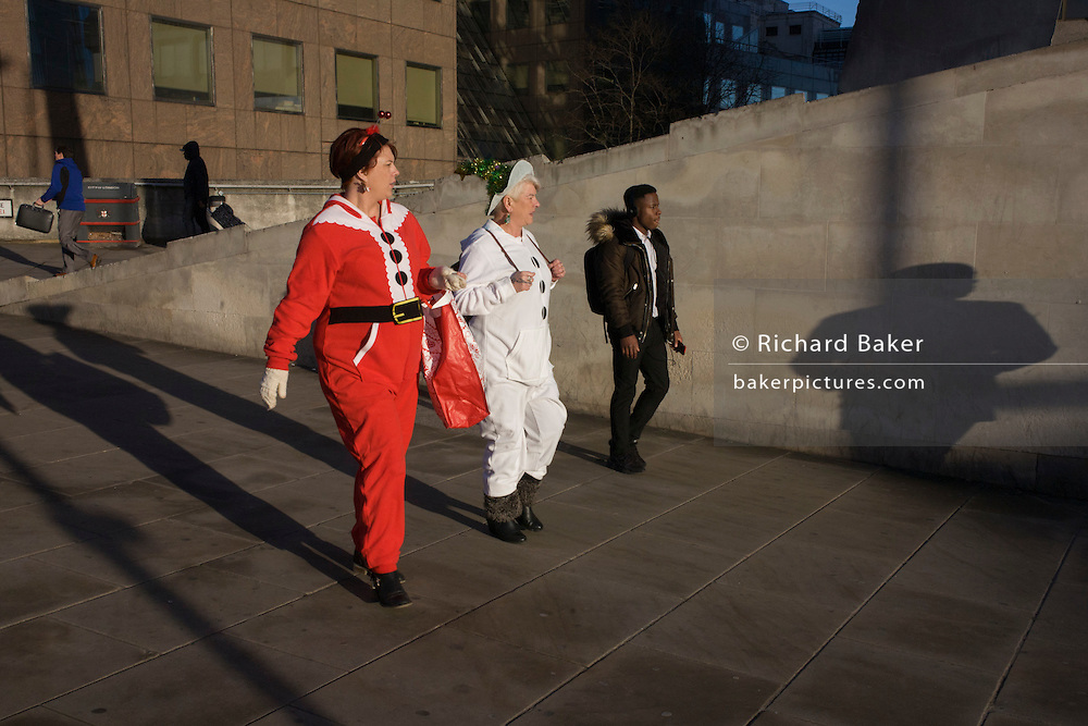 Women dressed in Christmas party costumes walk southwards from London Bridge into Southwark in central London