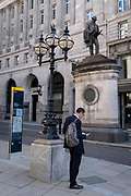 In the week that many more Londoners returned to their office workplaces after the Covid pandemic, a businessman reads paperwork beneath the statue of engineer James Henry Greathead, in the City of London, the capital's financial district, on 8th September 2021, in London, England. Civil engineer James Henry Greathead (1844 -1896), is renowned for his work on the London Underground.