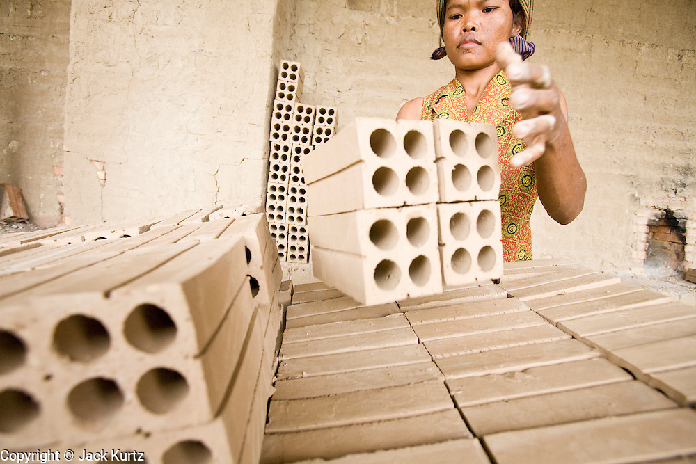 30 JUNE 2006 - PHNOM PENH, CAMBODIA: A woman stacks unbaked bricks on a cart before taking them to the kiln in a brick factory in Phnom Penh. According the United Nations Food and Agricultural Organization, there are more than 70 brick factories in Phnom Penh and its environs. Environmentalists are concerned that the factories, most of which burn wood in their kilns, contribute to deforestation in Cambodia. They are encouraging factory owners to switch to burning rice husks, as brick kilns in neighboring Vietnam do. The brick factories are kept busy feeding Phnom Penh's nearly insatiable appetite for building materials as the city is in the midst of a building boom brought by on economic development and the need for new office complexes and tourist hotels.   Photo by Jack Kurtz / ZUMA Press