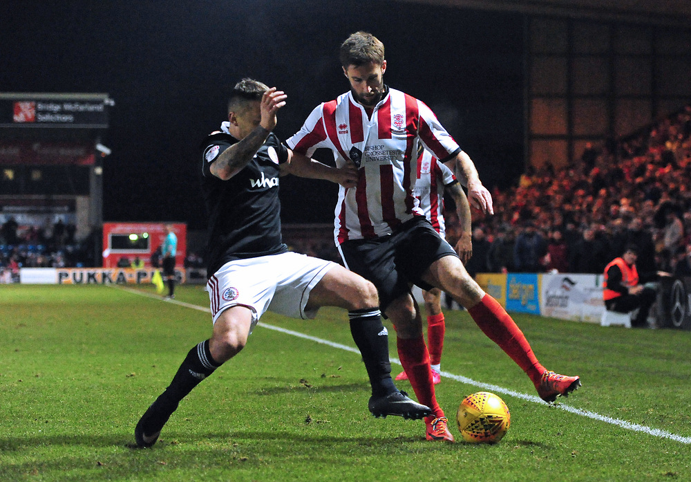 Lincoln City's Ollie Palmer vies for possession with Accrington Stanley's Scott Brown<br /> <br /> Photographer Chris Vaughan/CameraSport<br /> <br /> The EFL Sky Bet League Two - Lincoln City v Accrington Stanley - Saturday 16th December 2017 - Sincil Bank - Lincoln<br /> <br /> World Copyright © 2017 CameraSport. All rights reserved. 43 Linden Ave. Countesthorpe. Leicester. England. LE8 5PG - Tel: +44 (0) 116 277 4147 - admin@camerasport.com - www.camerasport.com