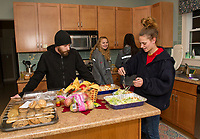 Anthony and Danielle serve up plates of lazagna and salad prepared by the LHS Key Club on Wednesday evening at the Belknap House.  (Karen Bobotas/for the Laconia Daily Sun)
