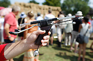 Photo by Andrew Tobin/Tobinators Ltd - 07710 761829 - 2012 world champion Rob Bresler's sophisticated laser sighted, balanced and chin supported pea shooter during the World Peashooting Championships held at Witcham, Cambridgeshire, UK on 13th July 2013. Run in conjunction with the village fair, the Championships have been held in Witcham since 1971 when they were started by a Mr Tyson, the village schoolmaster, in order to raise funds for the village hall.Competitors come from as far afield as the USA and New Zealand to attempt to win the event. The latest technology is often used, including laser sights and titanium and carbon fibre peashooters. All peashooters must conform to strict length rules, not exceeding 12 inches, and have to hit a target 12 feet away. Shooting 5 peas at a plasticine target attached to a hay bale, the highest scorers move through the initial rounds to a knockout competition, followed by a sudden death 10-pea shootout.