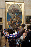 Tourist uses a digital camera to record the Mona Lisa in the Louvre, Paris.