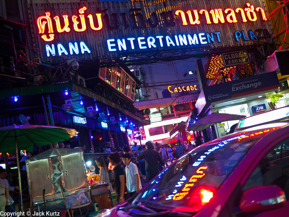 """13 JULY 2011 - BANGKOK, THAILAND:  A taxi passes the entrance to the Nana Entertainment Plaza, a """"red light"""" district in Bangkok. Prostitution in Thailand is illegal, although in practice it is tolerated and partly regulated. Prostitution is practiced openly throughout the country. The number of prostitutes is difficult to determine, estimates vary widely. Since the Vietnam War, Thailand has gained international notoriety among travelers from many countries as a sex tourism destination. One estimate published in 2003 placed the trade at US$ 4.3 billion per year or about three percent of the Thai economy. It has been suggested that at least 10% of tourist dollars may be spent on the sex trade. According to a 2001 report by the World Health Organisation: """"There are between 150,000 and 200,000 sex workers (in Thailand).""""  PHOTO BY JACK KURTZ"""