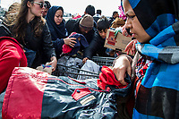 ATHENS, GREECE - FEBRUARY 04: A group of volunteers give winter hats to refugees arriving at the Pireaus port by ferries from the islands on February 04, 2015 in Athens, Greece. Dozens of volunteers work every day at the Pireaus port in Athens preparing food, drinks and items as hats, blankets among many others that they will give to the thousands of refugees arriving by ferries fleet by private companies from the Greek islands to the Pireaus port. Photo: © Omar Havana. All Rights Are Reserved