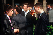 Two young 1990s city workers drink pints of beer outside a pub in the City of London aka The Square Mile, the capitals financial centre, on 20th May 1993, in London, England.