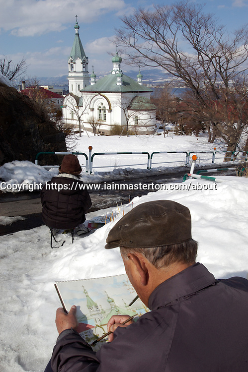 Man painting former Russian Orthodox church in Hakodate Hokkaido Japan