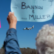 North Charleston, SC - Protestors hold up signs as President Donald Trump lands in Air Force One at Charleston International Airport. Once there, he will deliver remarks at the Boeing facility. (Logan Cyrus for AFP)
