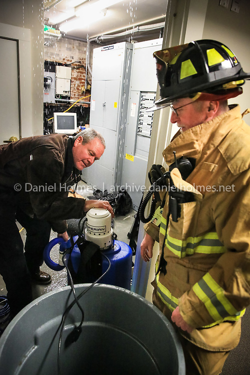 (1/4/14, HOLLISTON, MA) Firefighter Alan Elliott, and Capt. Dan Moulton work to remove water after a pipe burst at Town Hall in Holliston on Saturday. Daily News and Wicked Local Photo/Dan Holmes