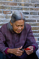 The ancient village of Yangmei is approximately 30 kilometres from the provincial capital of Nanning.  Ms Huang of Yangmei sits making tiny embroidered shoes in the grounds of Huang Manor.