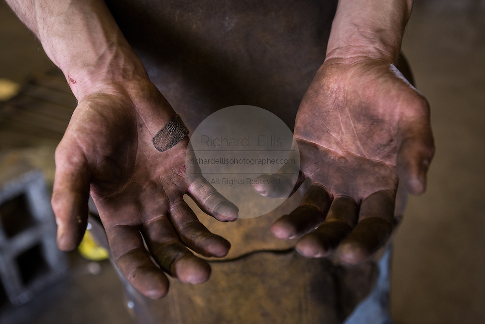 Blacksmiths hands covered in dirt in a metal working shop in Charleston, SC
