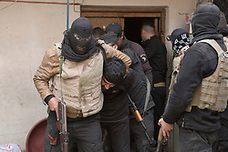Licensed to London News Pictures. 13/02/2017. Mosul, Iraq. A masked officer of the Iraqi National Security Service holds a suspected ISIS fighter in a headlock as a team mate cuffs the suspect's hands during a rain in eastern Mosul.<br /> <br /> The Jihaz Al-Amin Al-Watani, roughly translated as the National Security Service or NSS, are a secretive Iraqi agency that works under the responsibility of the Ministry of Interior. Since the liberation of eastern Mosul in January 2017 the NSS have been actively hunting down ISIS members who stayed behind to continue terrorism as part of sleeper cells and residents who worked with the group during its two year occupation. Recruiting from across the country agency is responsible for internal security inside Iraq and has a broad remit to investigate and arrest everything from terrorists and foreign spies to financial criminals and drug traffickers. Photo credit: Matt Cetti-Roberts/LNP