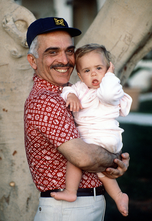 King Hussein of Jordan with his youngest daughter Princess Inman seen in the garden of their home in Aqaba, Jordan in May 1984. Photographed by Jayne Fincher