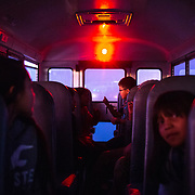 Lazayne Joe (center, 1st grade) and fellow dorm students ride on the Sunday dorm bus, December 1, 2019, en route to Hunters Point Boarding School, St. Michaels, Arizona. Dorm students are picked up Sunday afternoon and are bussed home Friday after school dismisses at 1pm.