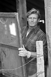 rugged handsome man holding an old wooden window in a barn