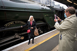 © Licensed to London News Pictures. 20/05/2021. London, UK. A passenger poses for a photograph before  boarding The LNER Flying Scotsman steam locomotive at Victoria Station in central London ahead of a tour through the Surrey Hills in South east England. The heritage steam locomotive touring season was mostly cancelled last year due to the Covid-19 pandemic but is now underway as restrictions are eased. Built in 1923 for the London and North Eastern Railway (LNER)It was the first steam locomotive to reach 100 miles per hour . Photo credit: Ben Cawthra/LNP