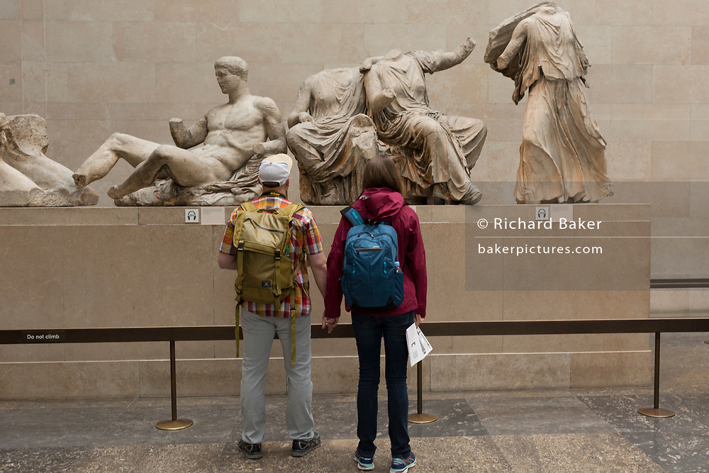 Visitors admire the sculpture of the ancient Greek Parthenon's Elgin Marbles Metopes in the British Museum, on 11th April 2018, in London, England.