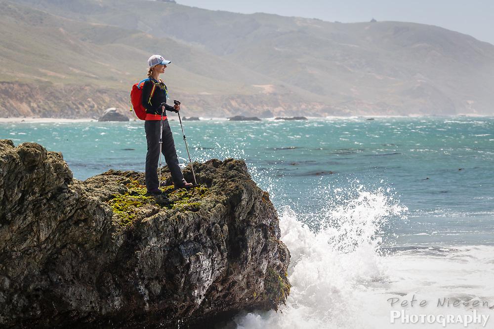 Female hiker on rocks above crashing ocean waves