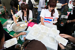 © Licensed to London News Pictures. 05/01/2014. Anti-Government protestors line up & are served free food courtesy of the PDRC during the third day of the 'Bangkok Shutdown' as anti-government protesters continue with their 'shutdown' of Bangkok.  Major intersections in the heart of the city have been blocked in their campaign to oust Prime Minister Yingluck Shinawatra and her government in Bangkok, Thailand. Photo credit : Asanka Brendon Ratnayake/LNP