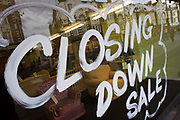 A closing down sale window is written with emulsion paint on glass in a London furniture shop. The reflection of the street behind can be seen with armchairs and cots. Around a recession-bled Britain, high-street businesses have been going bust in their thousands. Britain has now endured eight recessions since the Second World War. No two recessions are alike, and that applies to the current slowdown also. It has been caused by a shock to the availability of credit, a massive build up of debt. The number of people out of work currently stands at almost two million. Given the rate at which the economy is deteriorating this could easily be above three million. From a continuing piece of work about windows and urban messages, the picture is from the project of closed business windows: 'Bust - the Art of Recession'.