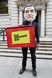 © Licensed to London News Pictures. 07/07/2015. London, UK. A protestor with a George Osborne head from the Tax Dodging Bill campaign demonstrates outside The Treasury in London against 'multi-national tax avoidance' ahead of the Budget and call for George Osborne to introduce a tax dodging bill. Photo credit : Vickie Flores/LNP