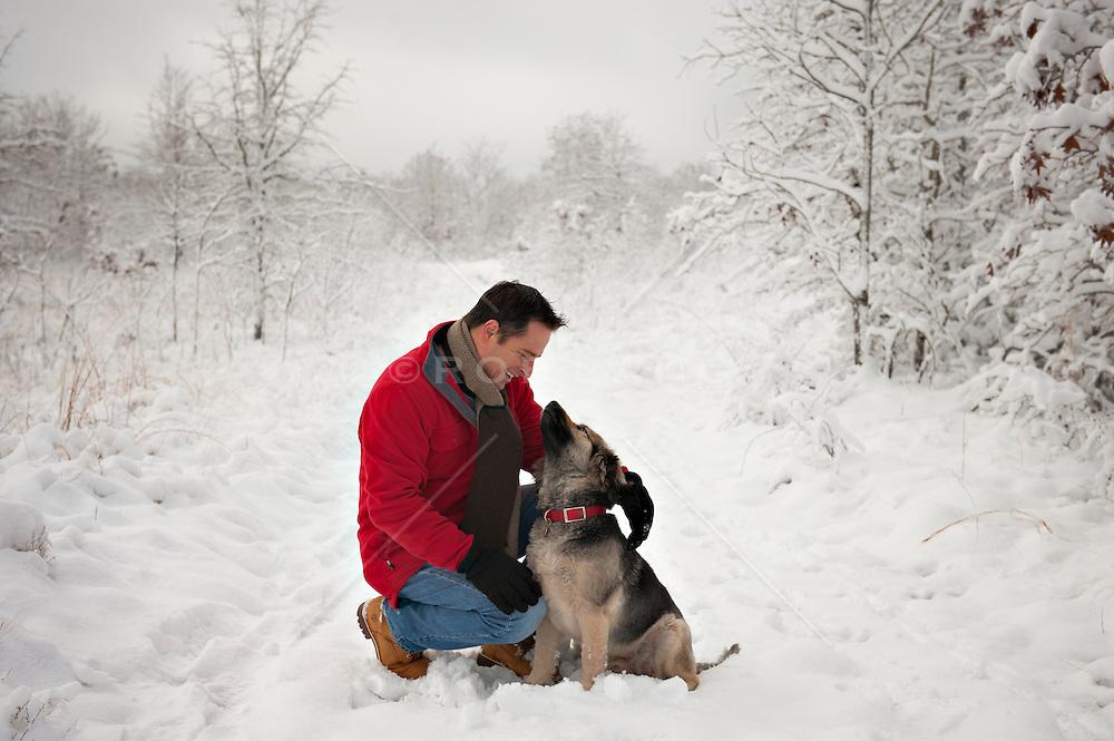 man enjoying his dog in the snow