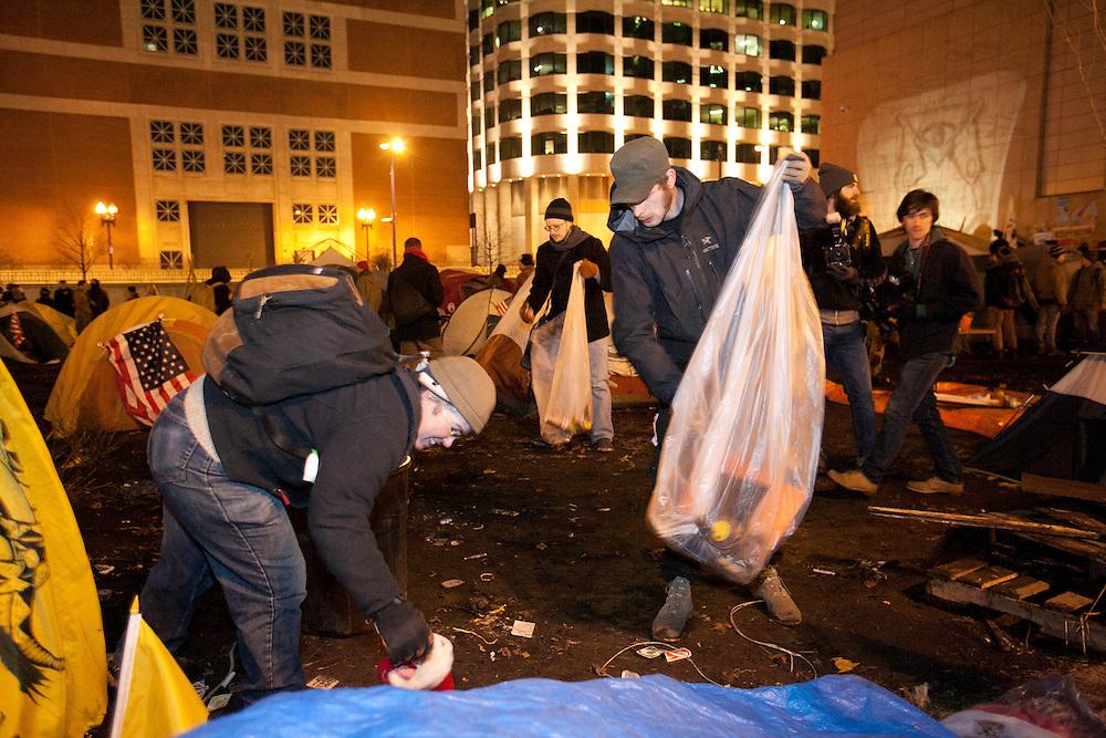 Boston, MA 12/08/2011.Occupy Boston members pick up trash from Dewey Square on Thursday night..Alex Jones / www.alexjonesphoto.com