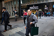 People rush to work in Central district, a man with a green bag and a cigaret.7 million people live on 1,104km square, making it Hong Kong the most vertical city in the world.