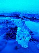 Surreal iceberg on gravel bar in stream flowing through glacial ice cave, Glacier Bay National Park, Alaska.