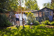 Family barbecue in garden with small child playing on 30th May, 2021 in London, United Kingdom.