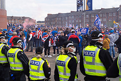 Glasgow, Scotland, UK. 15 May 2021. Hundreds of supporters and fans of Rangers football club descend on Ibrox Park in Glasgow to celebrate winning the Scottish Premiership championship. Smoke bombs and fireworks are being let off by fans tightly controlled by police away from the stadium entrances.Iain Masterton/Alamy Live News