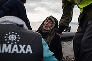 An elderly lady from Afghanistan is helped off a dinghy by volunteers and other migrants and refugees traveling with her, on the Greek island of Lesvos.