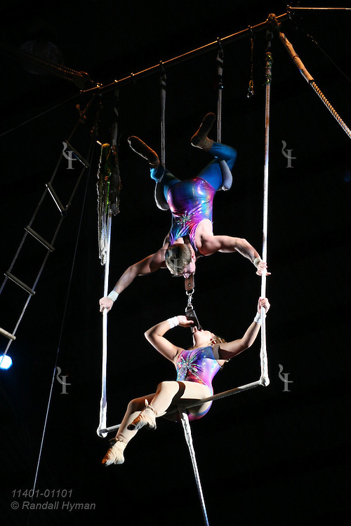 Teen couple performs double trapeze act as boy suspends girl from his neck at Peru Amateur Circus; Peru, Indiana.