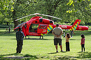 People observe an air ambulance helicopter that landed inside Southwark Park in Bermondsey, London to deliver an NHS emergency medical response unit to a road traffic accident after a motorbike and a car collided in Lower Road intersection with Neptun Street near Canada Water Station on Monday, May 4, 2020. (Photo/ Vudi Xhymshiti)