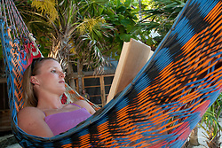Central America, Honduras, Bay Islands, Utila, Utopia Village, woman reading in hammock MR