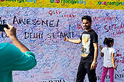People photograph each other in front of a wall covered in graffiti on a road blocked to cars in a section of Connaught Place during a Raahgiri Day. Raahgiri Day is India's first sustained car-free citizen initiative that started in Gurgaon but has since spread across India. Here, Connaught Place is closed to traffic and community events are held. New Delhi, India