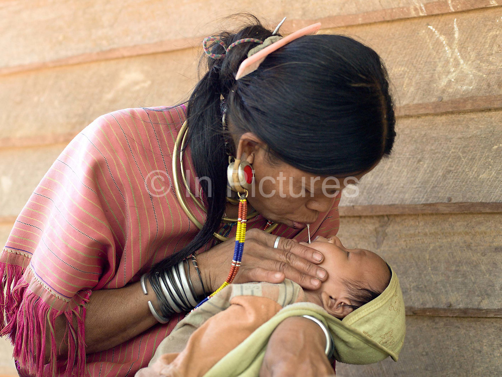 An ethnic Kayaw woman feeding her baby chewed rice in a traditional way on 27th March 2016 in Kayah State, Myanmar. Myanmar is one of the most ethnically diverse countries in Southeast Asia with 135 different indigenous ethnic groups with over a dozen ethnic Karenni subgroups in the Kayah region. Wearing traditional costumes made from handwoven cotton, Kayaw women wear many necklaces made from shells, beads and brass coils and fashioned from silver. Distended earlobes are plugged with rings of silver and the ankles and knees encased with brass coils