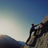 A climber ascends a boulder in the Buttermilk Rocks, near Bishop, California.  Mount Tom in the Sierra Nevada rises behind him.