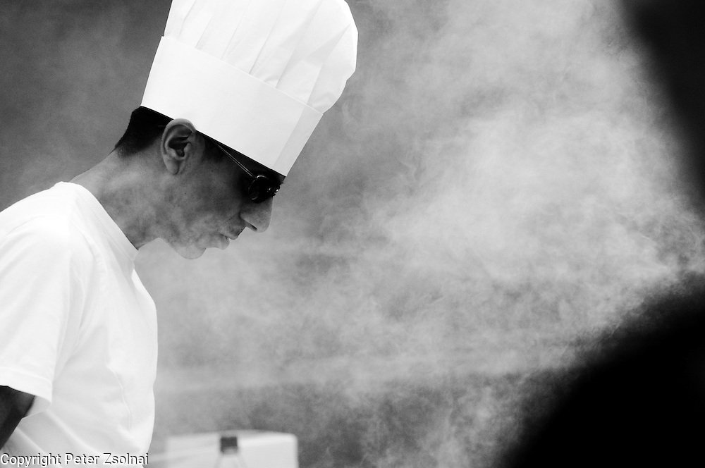 A chef is cooking in a street of Berlin preparing some sort of street-food