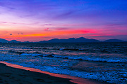 Sunset at An Bang Beach, Vietnam. Before a big storm this sunset showed up. There was smoke in the air after rice farmers burned the remnants of crop, the straw. (Will print with a small amount of grain)
