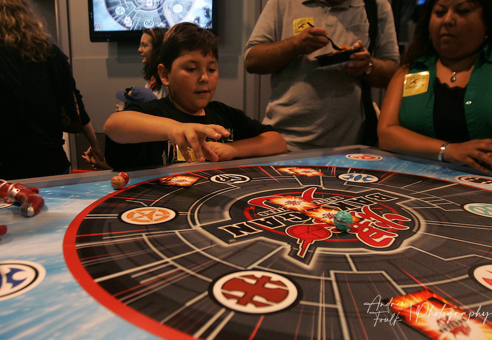 """/Andrew Foulk/ For The North County Times/.Trevor Sullivan, 10, of Santee, gets a lesson on how to play """"Bakugan"""" a dice and card game, during preview night at the 40th annual San Diego Comic Con International."""