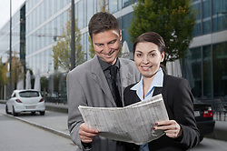Business executives reading a financial newspaper and smiling, Bavaria, Germany