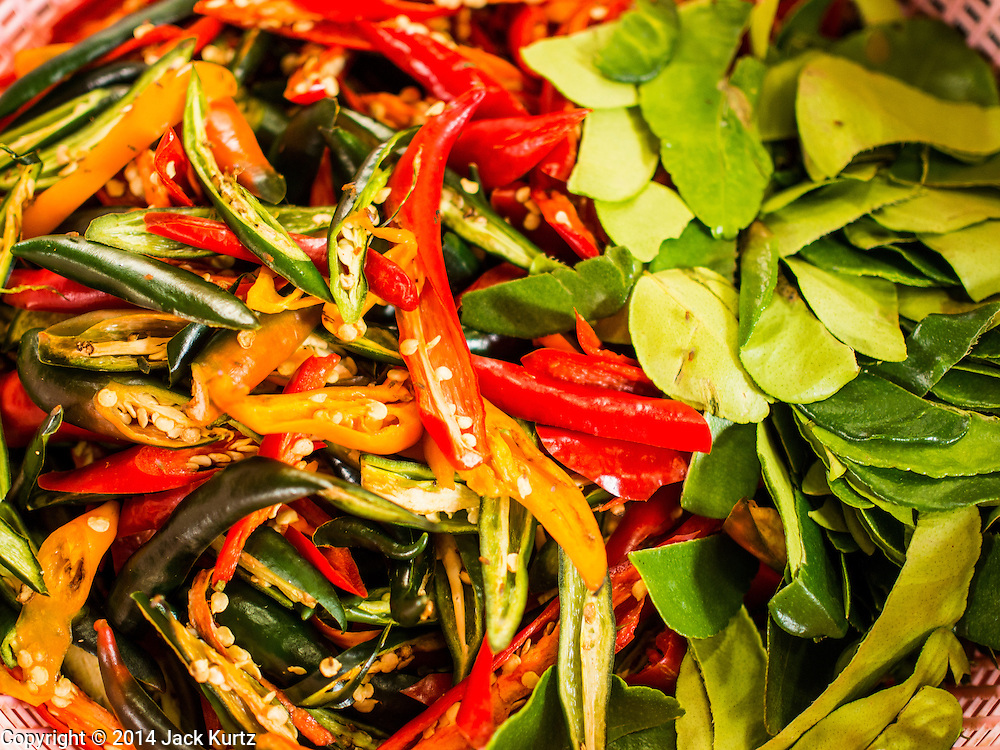 """09 AUGUST 2014 - BANGKOK, THAILAND: Chillies and kaffir lime leaves used in preparing meals at the Ruby Goddess Shrine in the Dusit section of Bangkok. The seventh month of the Chinese Lunar calendar is called """"Ghost Month"""" during which ghosts and spirits, including those of the deceased ancestors, come out from the lower realm. It is common for Chinese people to make merit during the month by burning """"hell money"""" and presenting food to the ghosts. At Chinese temples in Thailand, it is also customary to give food to the poorer people in the community.        PHOTO BY JACK KURTZ"""