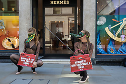 London, UK. 8th September, 2021. Two PETA supporters wearing Venetian crocodile masks pose outside the Hermès store in New Bond Street in protest against the luxury fashion house's use of exotic skins. PETA's campaign was launched following the release of video footage by The Kindness Project showing crocodiles being mutilated, electrocuted, stabbed and shot on farms in Australia with ties to Hermès and PETA are calling on the fashion brand to cease using exotic skins for their products.