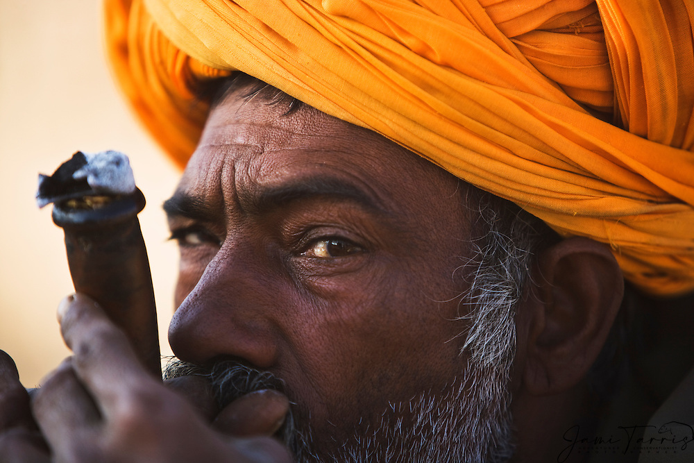 A close-up portrait of a camel trader smoking a pipe at the Pushkar camel fair, Pushkar,Rajasthan, India