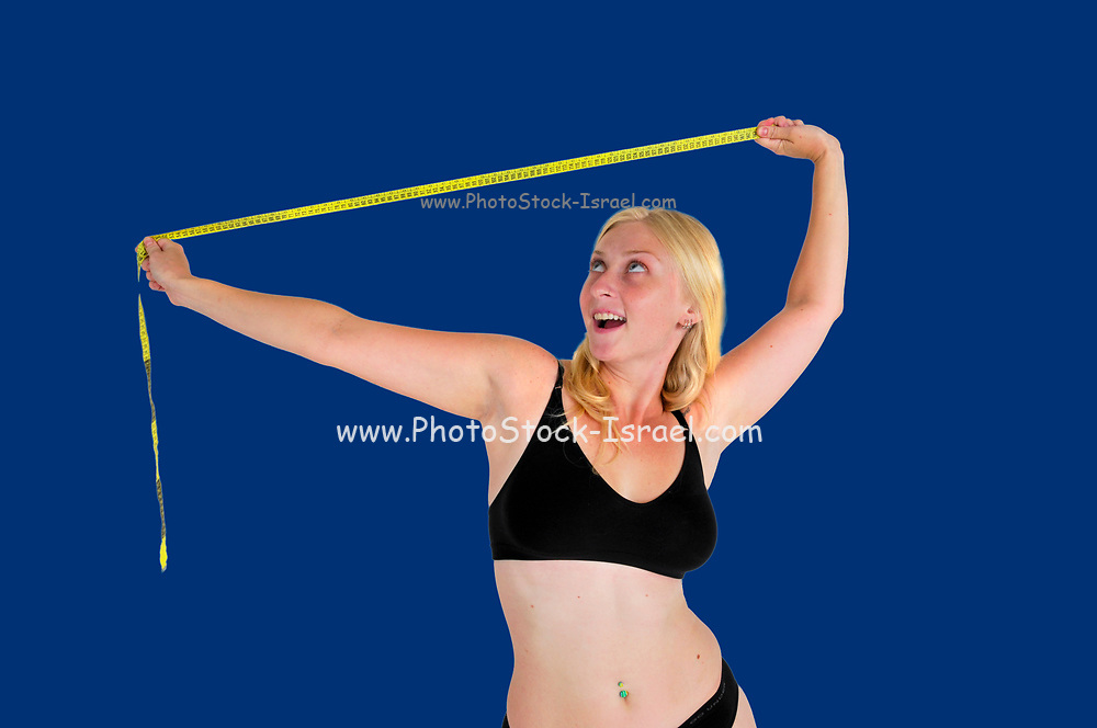 Young woman laughs at a tape measure. She has overcome compulsive body analysis caused by body image disorder such as anorexia nervosa. Model released on blue background